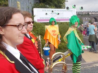 Burbage Band waits to join the Carnival Parade alongside the three-eyed monsters from the planet Zog - also Sam Slide's front of house team! (SS 2019)