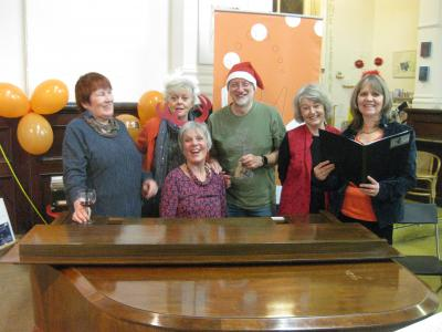From left to right: Jane Reynolds (choir), The Green Man Gallery's Caroline Small, Fringe entries co-ordinator Ian Bowns, Joan Knox (choir) and marketing officer Stephanie Billen with choir leader Carol Bowns at the piano, all having fun at the Fringe Christmas Party 2019.